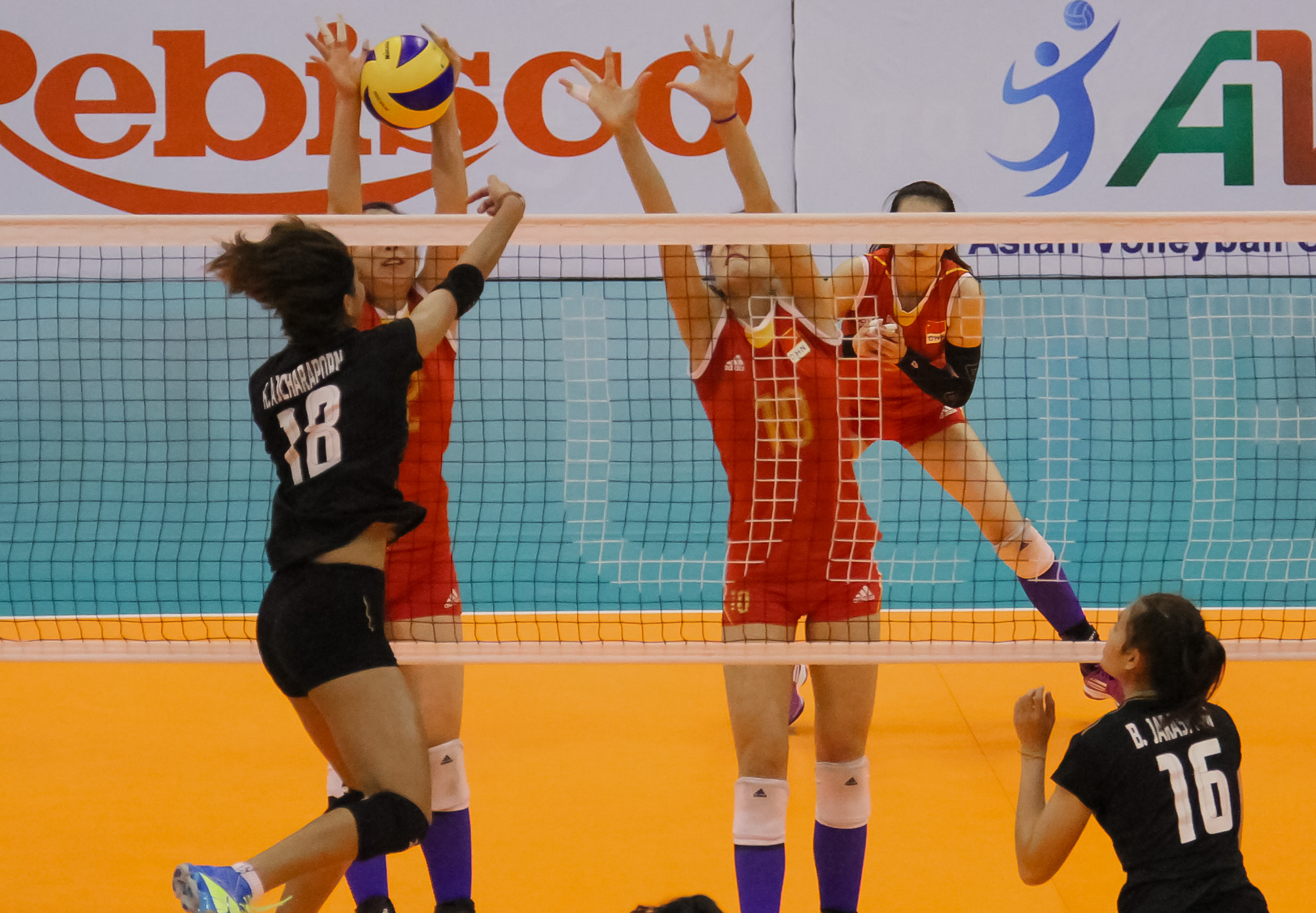 Thailand's Ajcharaporn Kongyot spikes against two Chinese blockers